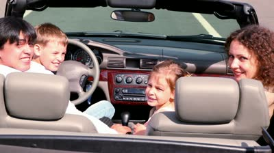 stock-footage-parents-and-two-kids-sit-in-cabriolet-and-look-backward-then-turn-view-from-behind-at-sunny-day.jpg