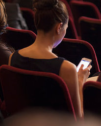 6113-07160098 © Masterfile Royalty-Free Model Release: Yes Property Release: Yes Rear view of woman using cell phone in theater audience