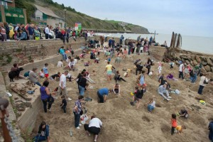 Folkstone Triennial opens. Opening day featured a hunt for 30 pieces of gold buried on the beach by artist Michael Sailstorfer.