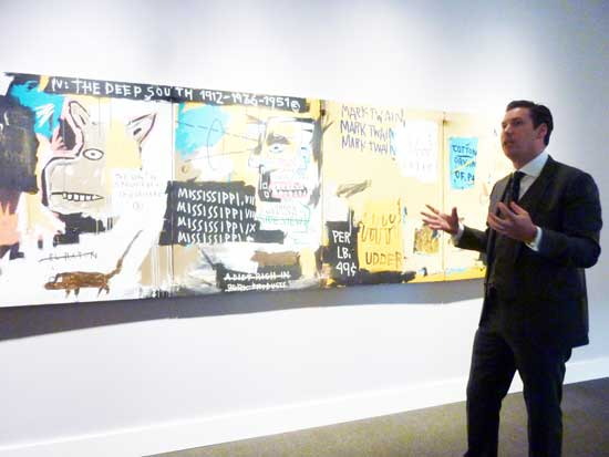 "Alex Rotter, Sotheby's Co-Head of Worldwide Contemporary Art. in front of Basquiat, ""Undiscovered Genius of the Mississippi,"" 1983 Photo by Lee Rosenbaum"