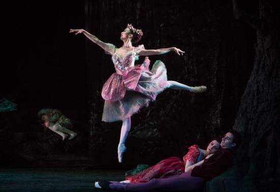 Fairy Peaseblossom (Akane Takada) flies above the slumbering lovers (Christina Arestis and Valeri Hristov in Frederick Ashton's The Dream. At left, alone: Johannes Stepanek Photo: Yi-Chun Wu