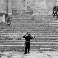 A soldier watches as a fiddler plays a tune in the ruins of Baalbek, Lebanon. A somewhat perfect juxtaposition and incredibly beautiful reminder. (C) Taylor Craig